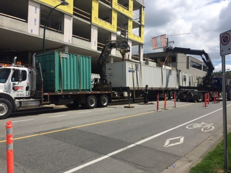 Placing containers that acted as temporary walk-through sidewalks during some heavy duty construction.