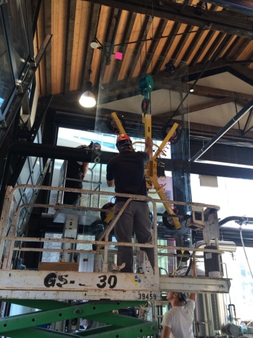 Using a Spyder Crane to help MJD Glass place glass inside the building now known as Steel Toad Brewpub & Dining Hall