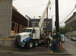 Stinger placing a 65 ft beam, taken over this sign on Main Street & Broadway in Vancouver